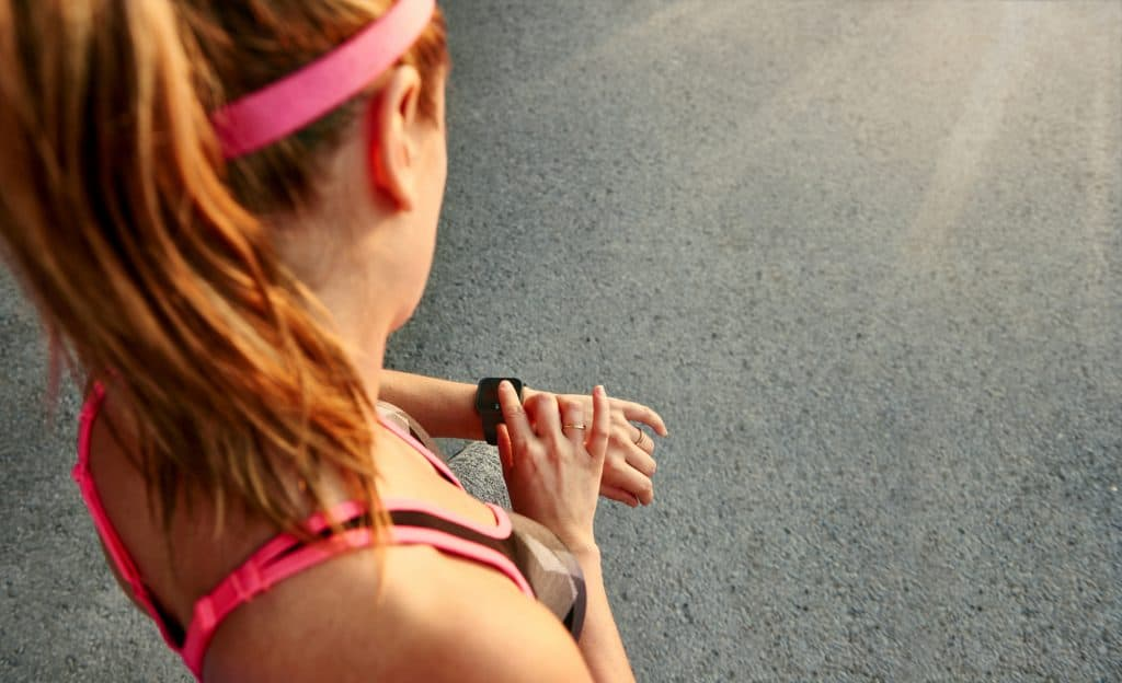 woman outdoors looking at her fitness watch