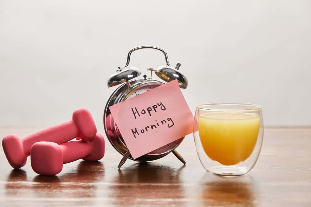 picture of pink weights, alarm clock, and orange juice. decorative image to illustrate healthy concept in an article about how to make exercise a habit.