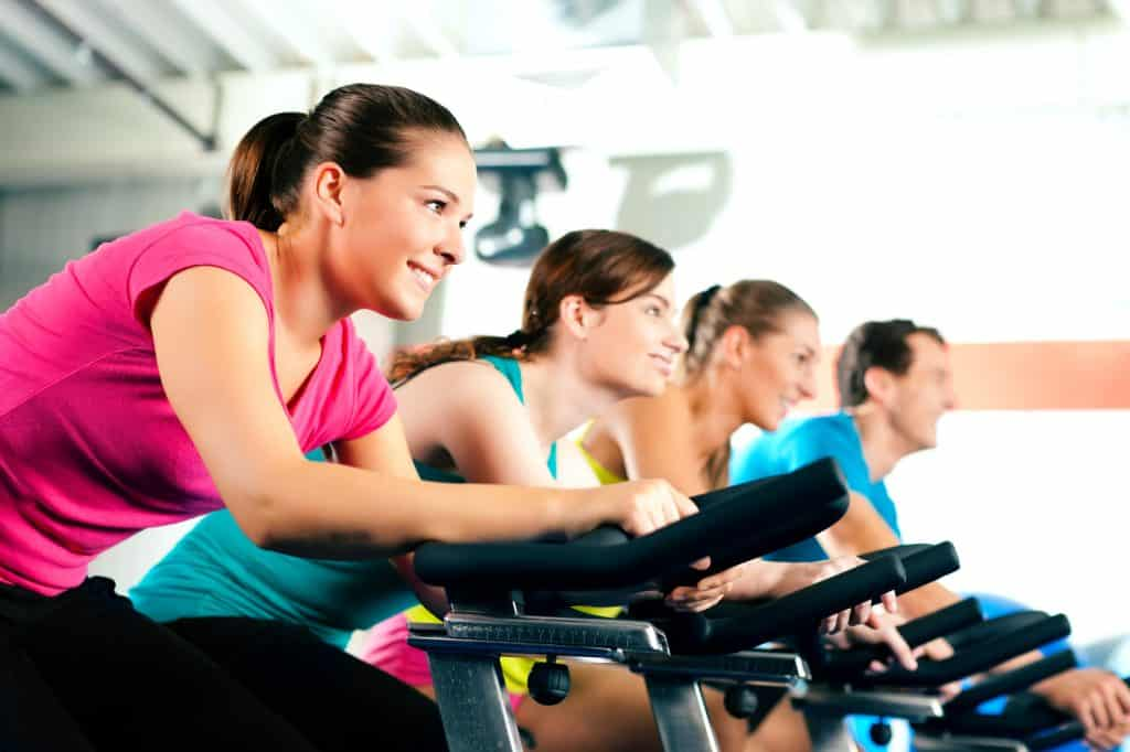people riding spin bikes in a spin class. A decorative image to demo cardio exercise examples in an article about how to build a well-rounded fitness routine.