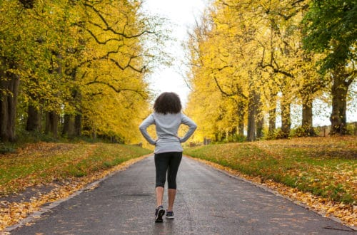 Beautiful Mixed Race African American Young Woman Girl Teenager Preparing For Fitness Running Jogging On Road Of Autumn Fall Trees