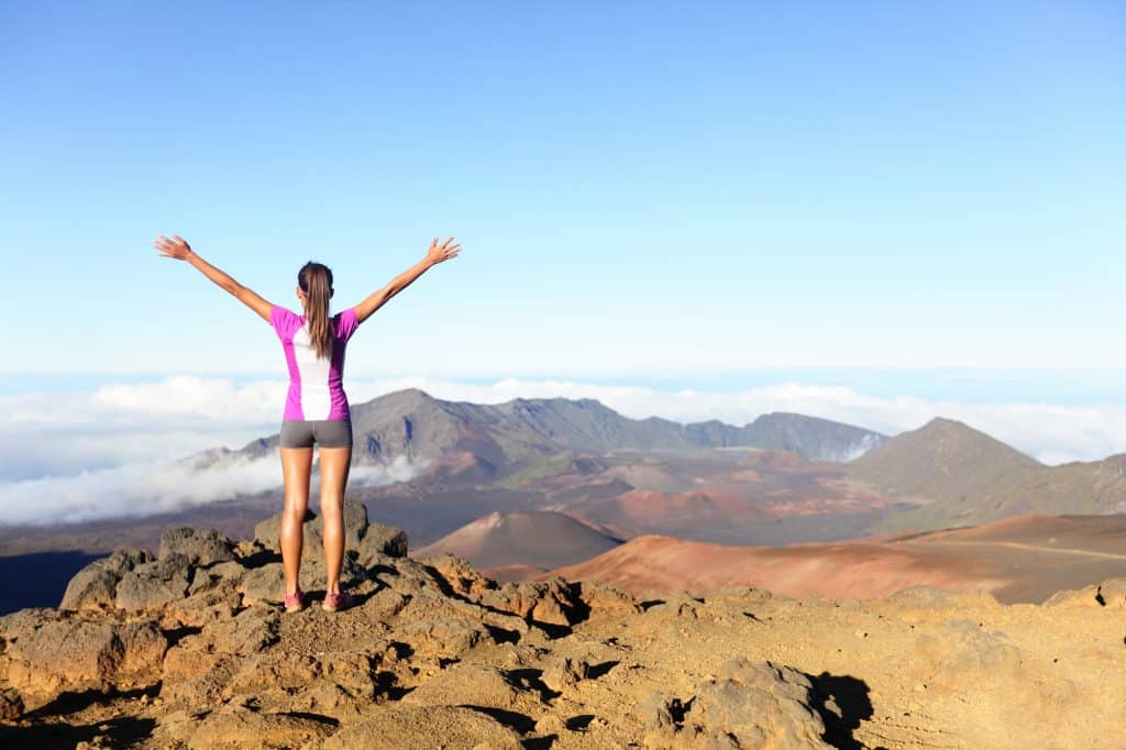 woman standing on a mountain with her arms in the air symbolizing success