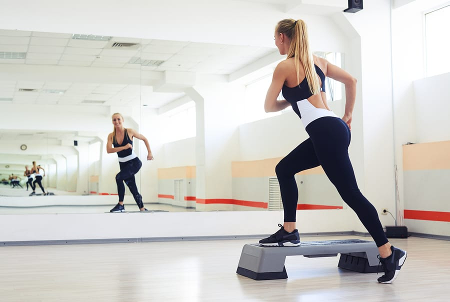 woman in a gym doing step aerobics low impact exercise