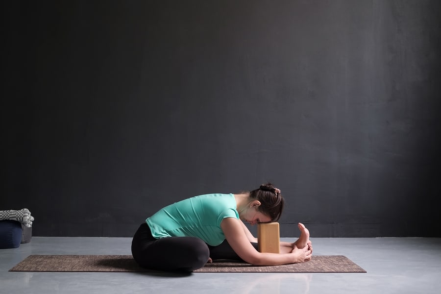 woman in seated half forward fold using a yoga block