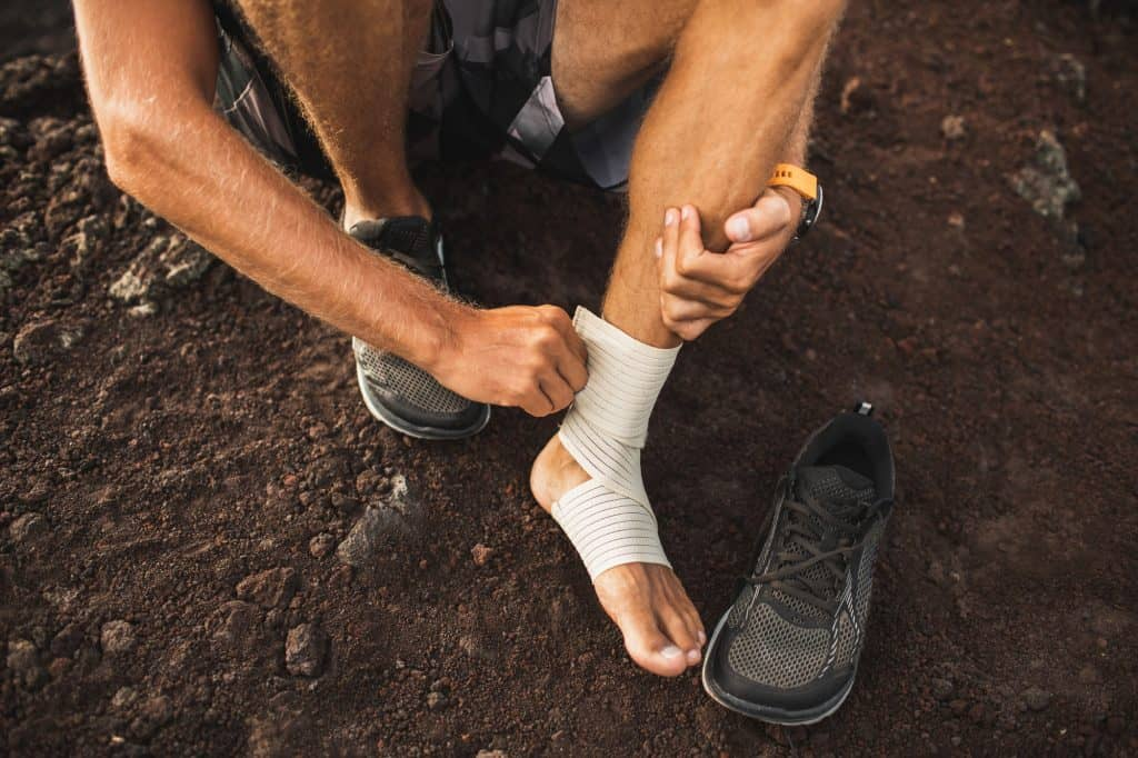 athletic man wrapping his foot due to plantar fasciitis