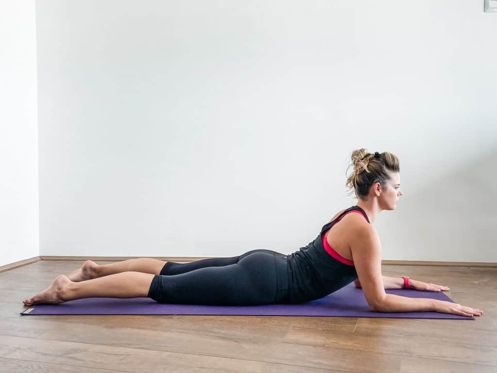 woman on a yoga mat performing sphinx pose