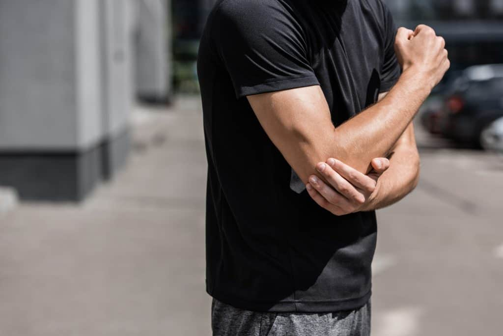 man holding his elbow due to pain from tennis elbow