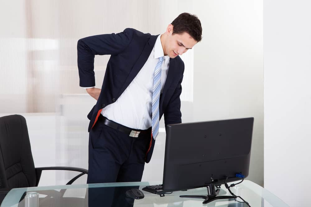 man at a desk with a backache. decorative image in an article about standing desk pros and cons