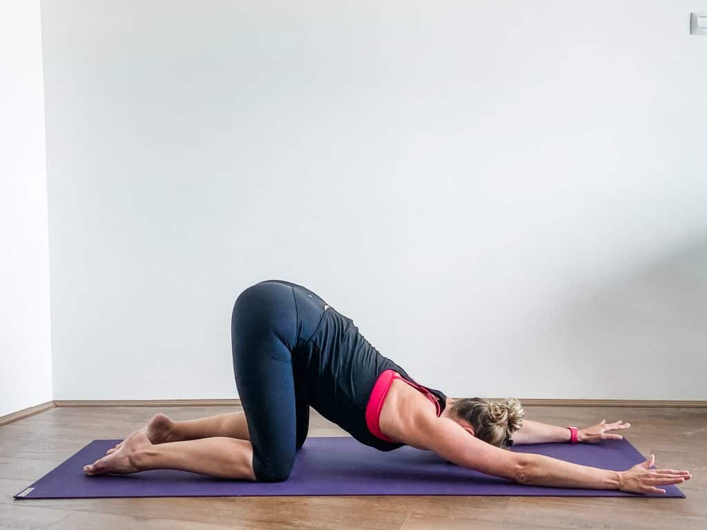woman on a yoga mat demonstrating a puppy pose stretch