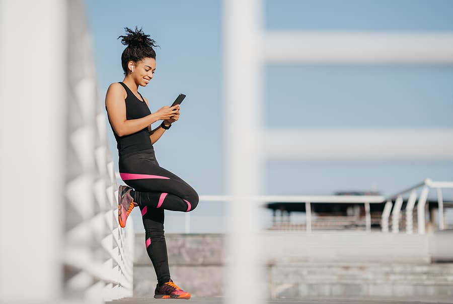 woman using a smartphone fitness app for a workout