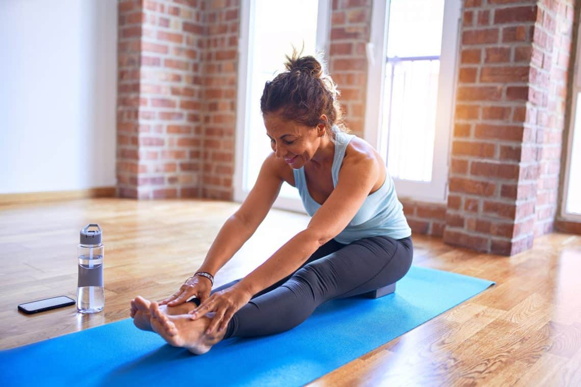 woman using a yoga block during yoga how to protect the hamstrings yoga for hamstrings