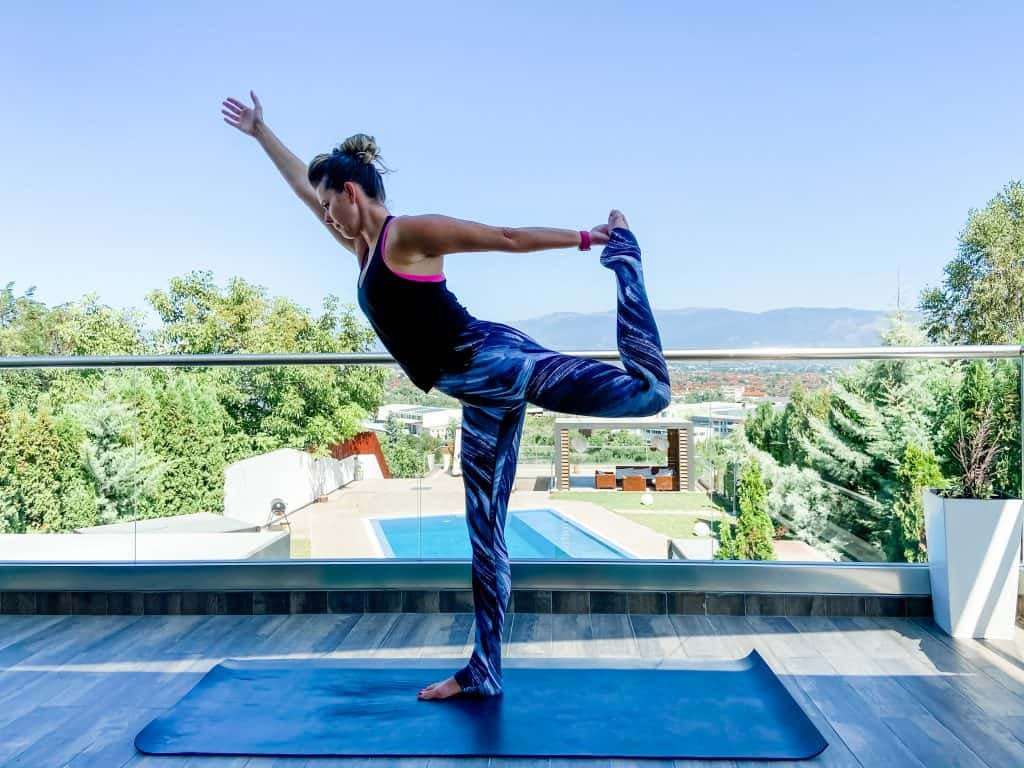 woman doing dancer pose on a yoga mat with a resort in the background - yoga mats for sweaty hands