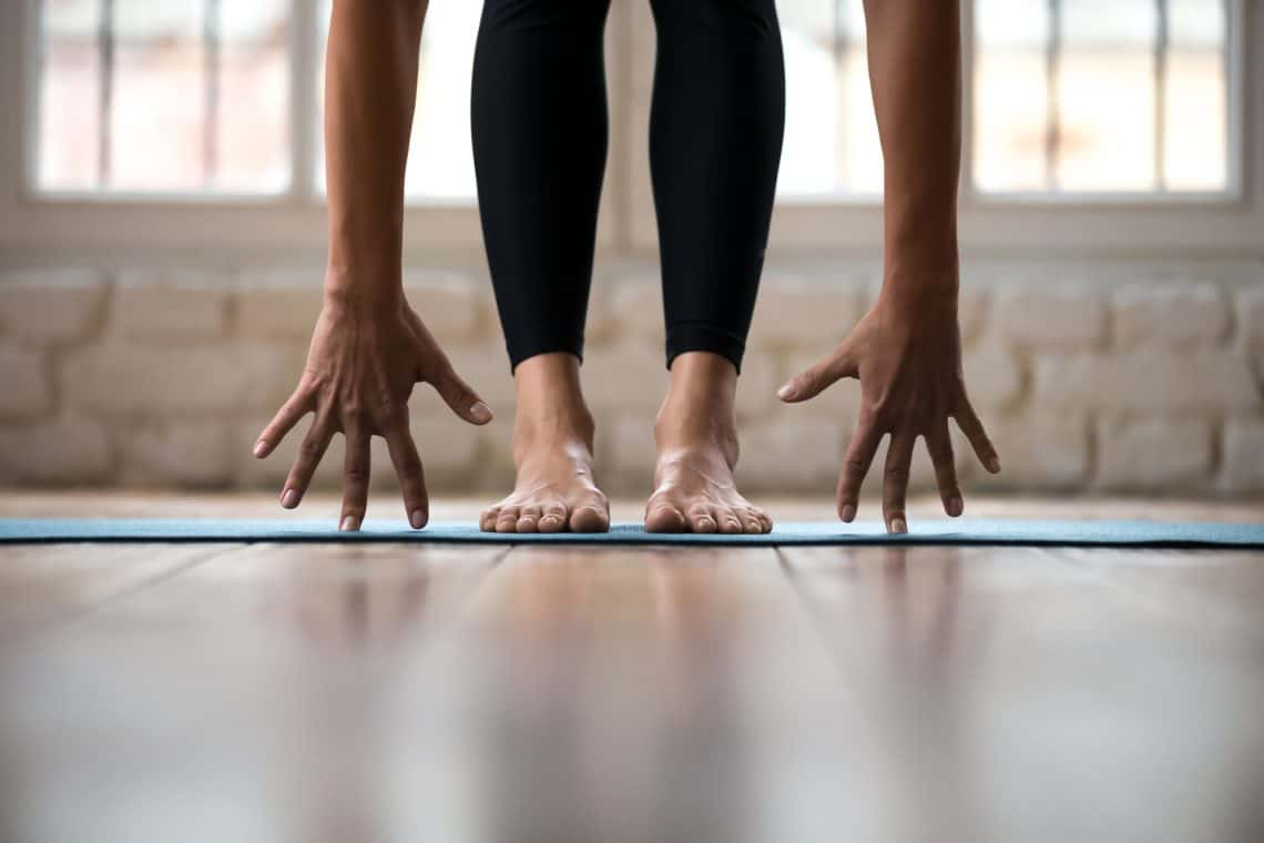 woman's feet and hands on a yoga mat decorative featured image for article about yoga mats for sweaty hands