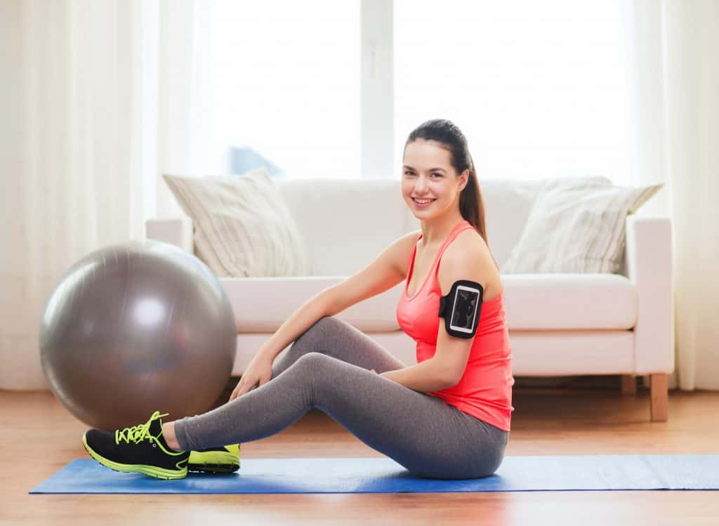 woman at home sitting on an exercise mat next to an exercise ball best physical therapy equipment for home