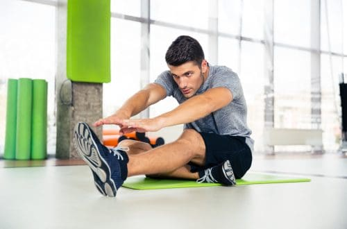 a man sitting on the floor in a gym trying to stretch his hamstrings mobility vs. flexibility