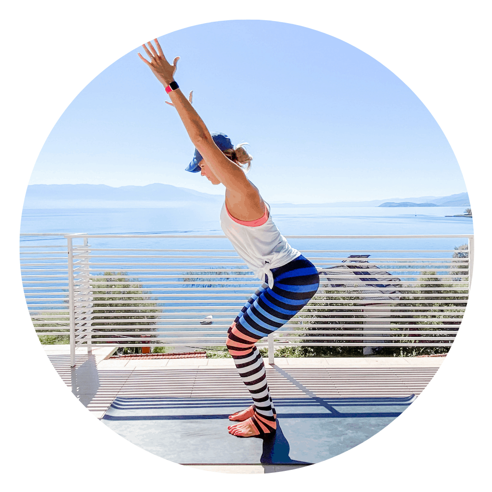 woman on a yoga mat doing chair pose outdoors with view of the mountains and lake