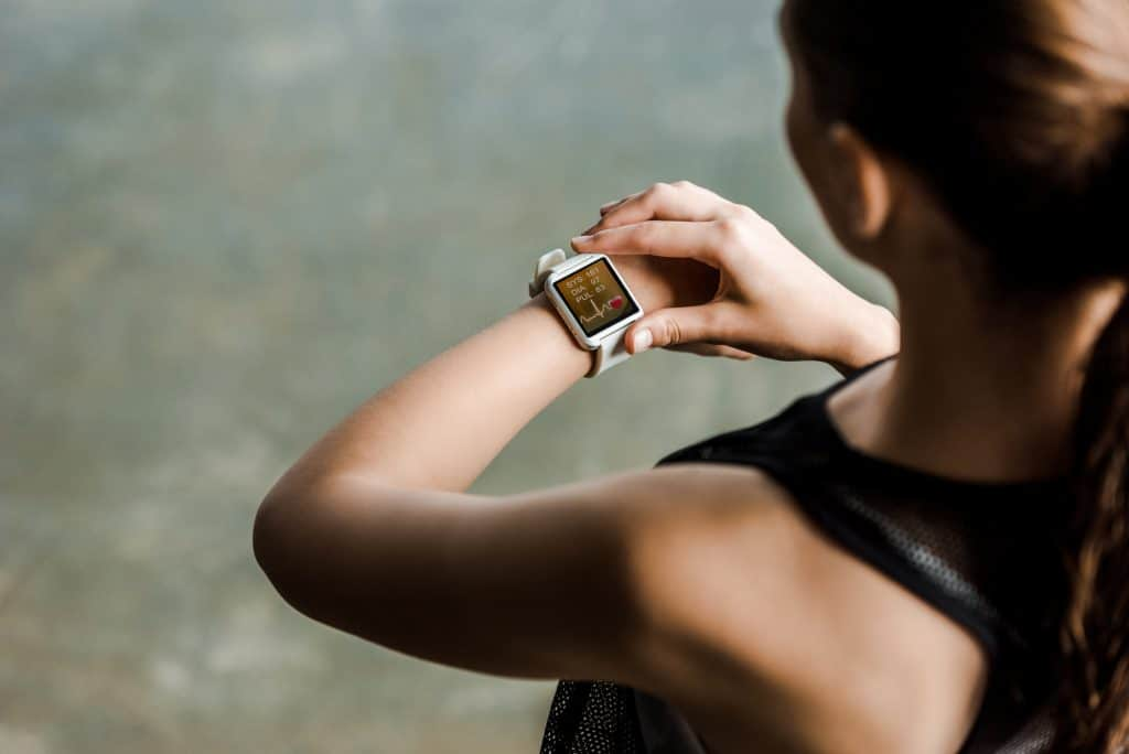 woman looking down at her fitness watch, a decorative image in an article about workout accessories