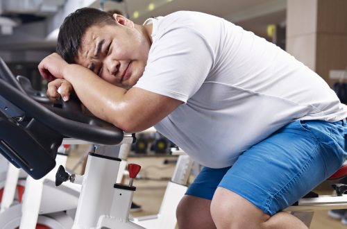 a man lying on a bike at the gym not enjoying exercise