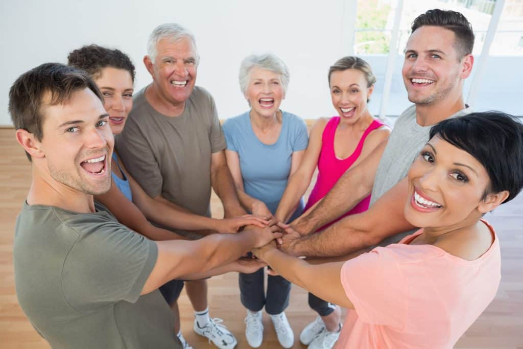 group of people at a fitness class with hands in how to be more active
