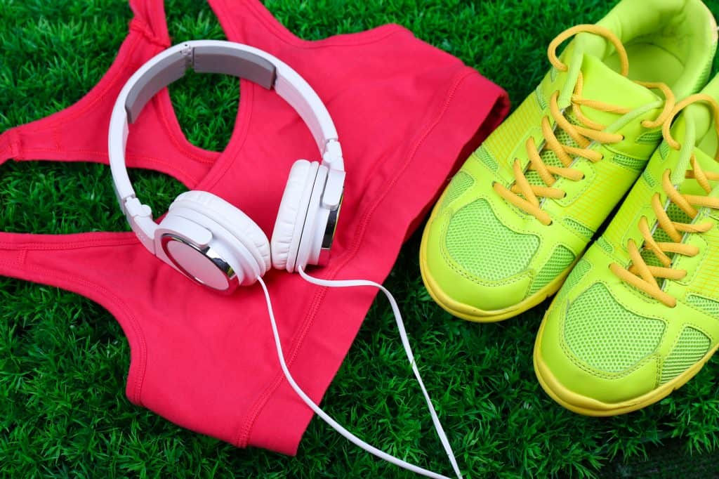 flatlay image of headphones, sneakers, and workout gear as a decorative image for an article about fitness accessories