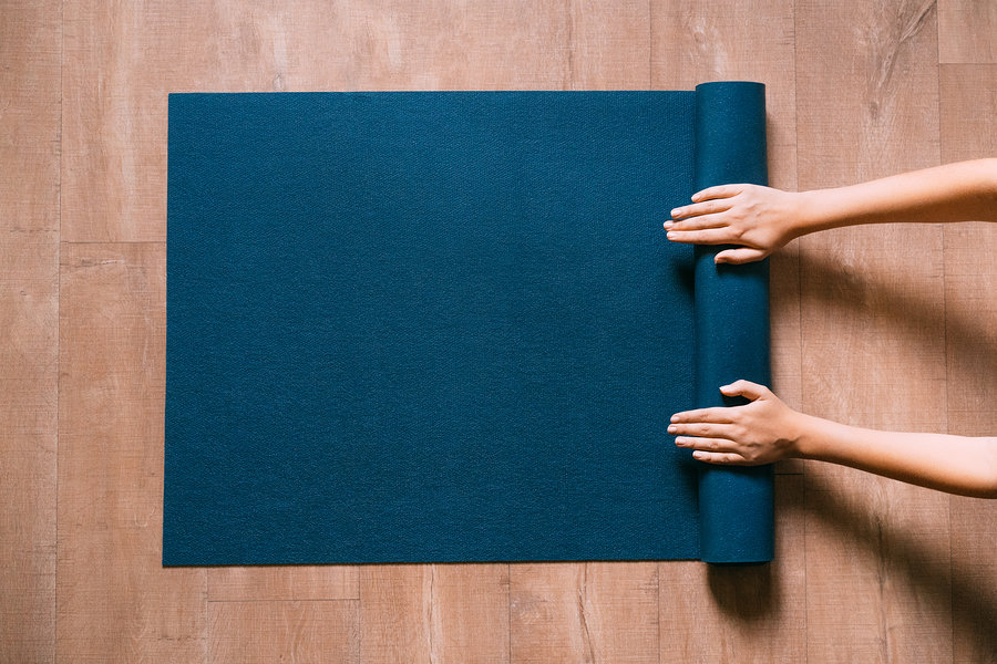 woman's hands unrolling a yoga mat on the floor