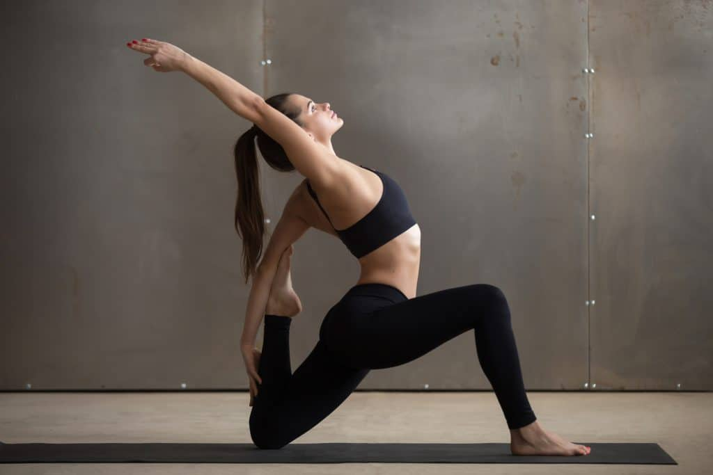 woman performing a hip flexor stretch in a yoga studio