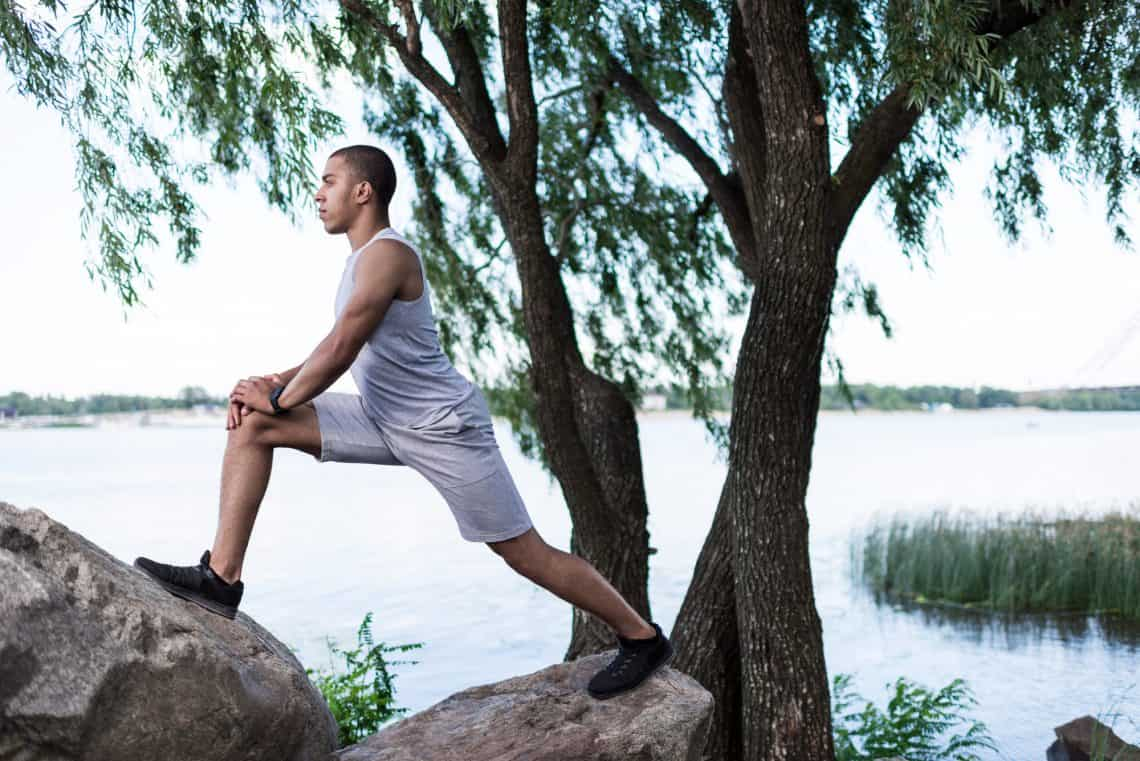 a man stretching his hip flexors by a river while working out