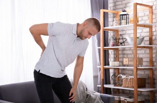 a man holding his back in pain as a decorative image for an article about what to avoid with sciatica