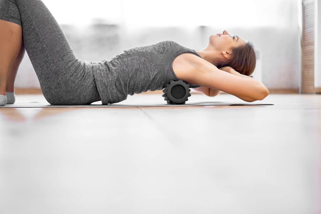 woman using a foam roller on her back