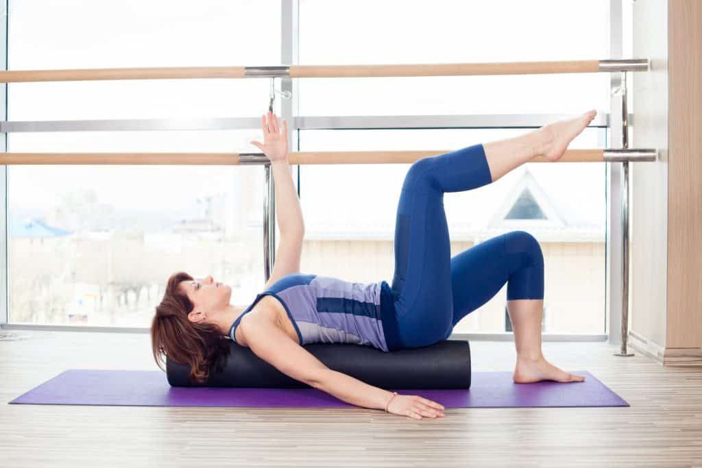 woman using a foam roller for stability exercises