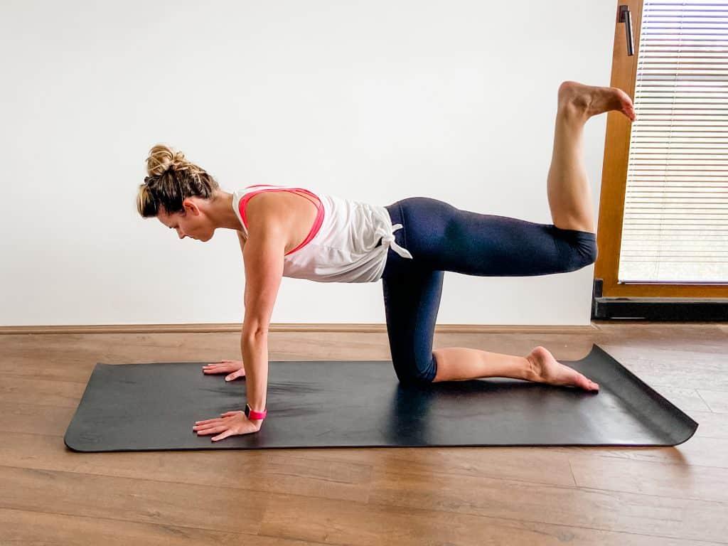 woman demonstrating donkey kick glute strengthening exercise