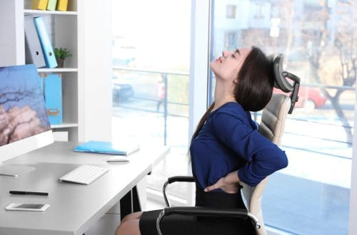 woman sitting at a desk stretching her back. decorative cover image for an article about how to improve your posture