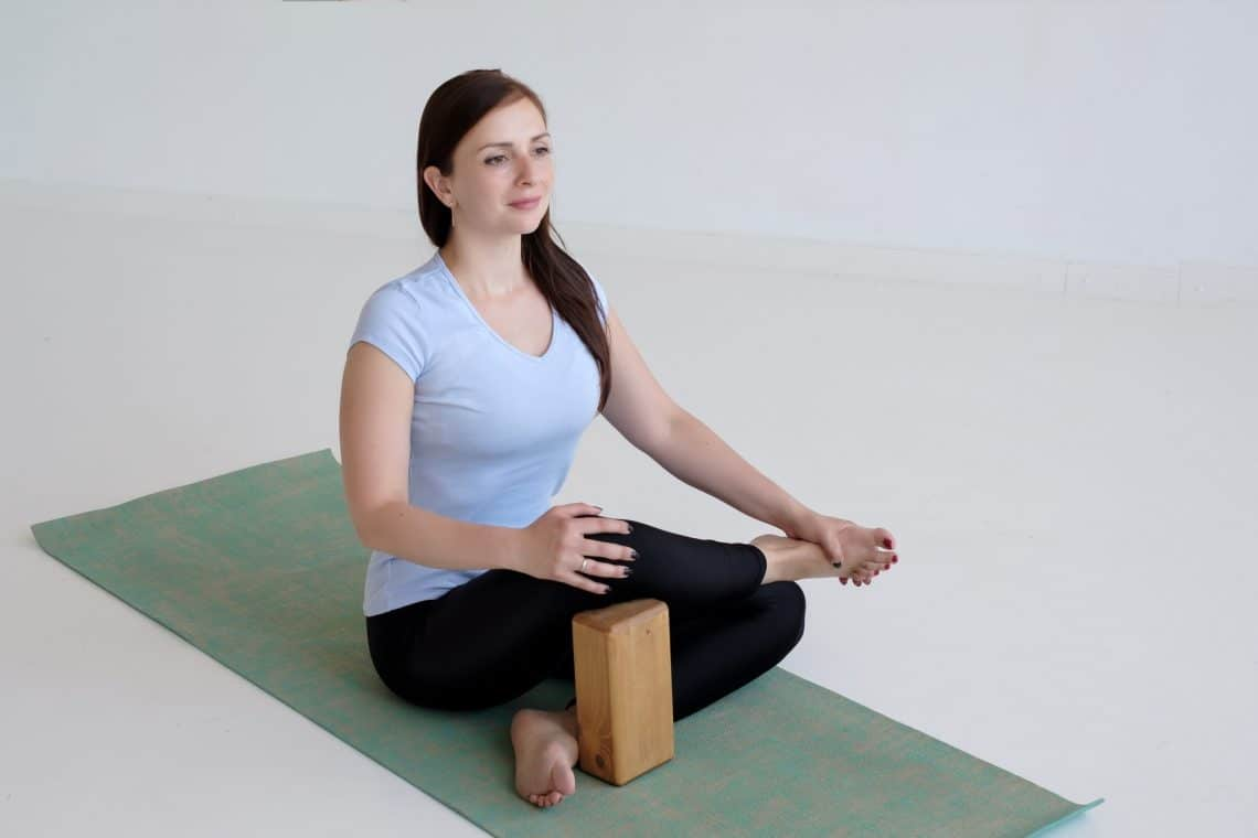 woman on a yoga mat using a block for knee support for yoga