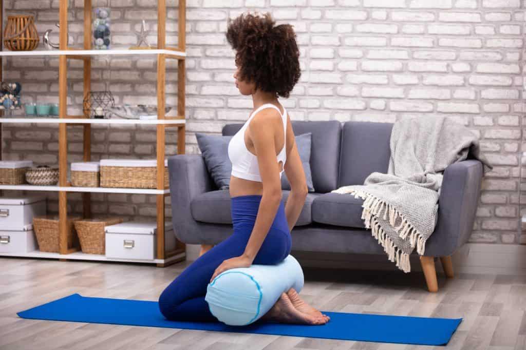 a woman using a bolster to modify a yoga pose