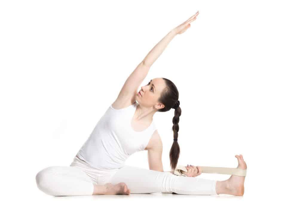 woman using a yoga strap to modify a yoga pose