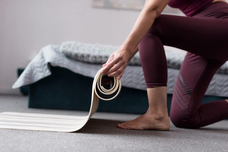 a woman unrolling a yoga mat for home yoga