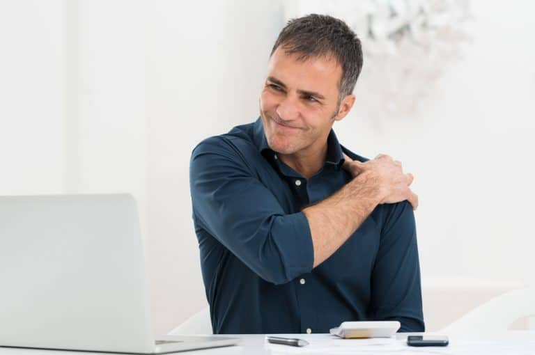 a man holding his shoulder in pain. decorative image for an article about shoulder impingement pain.
