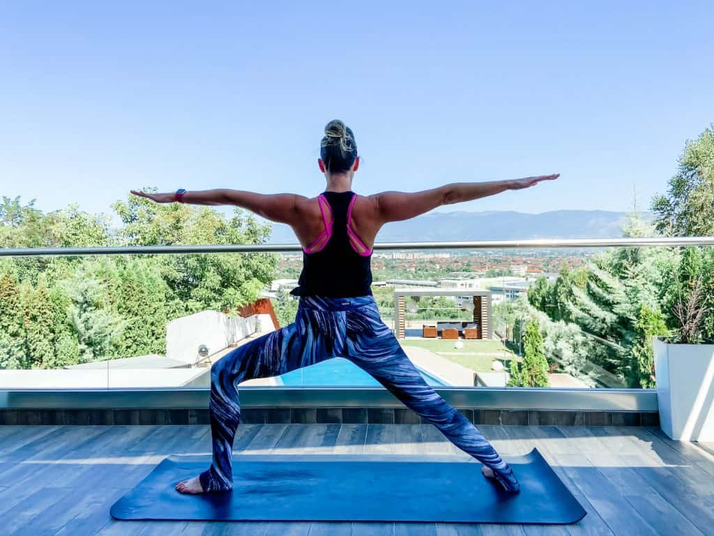 woman outdoors on a yoga mat demonstrating warrior 2