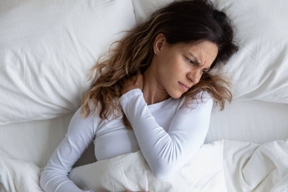 woman in bed holding her neck symbolizing neck pain from sleeping wrong