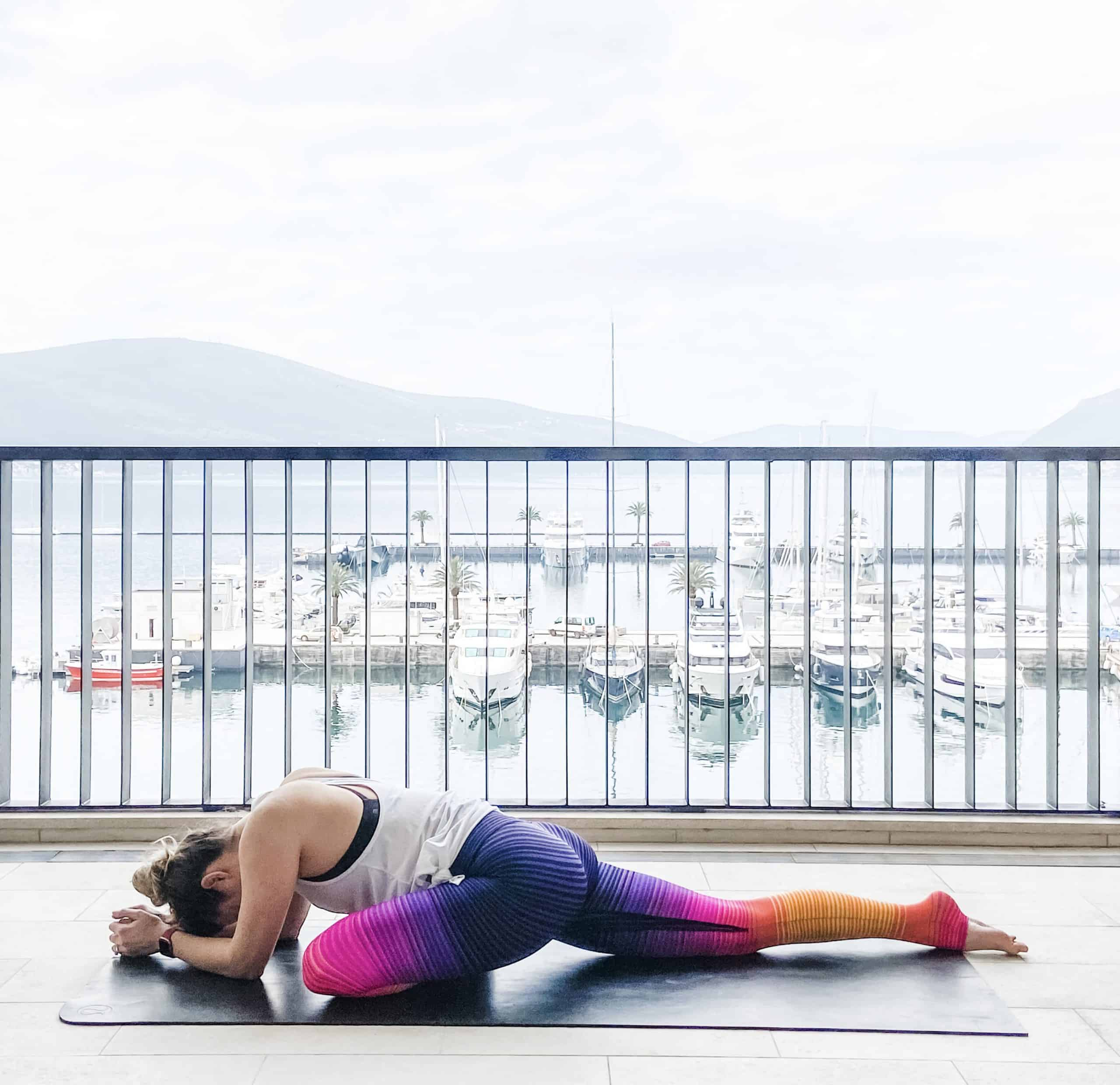 woman on a yoga mat outdoors in pigeon pose