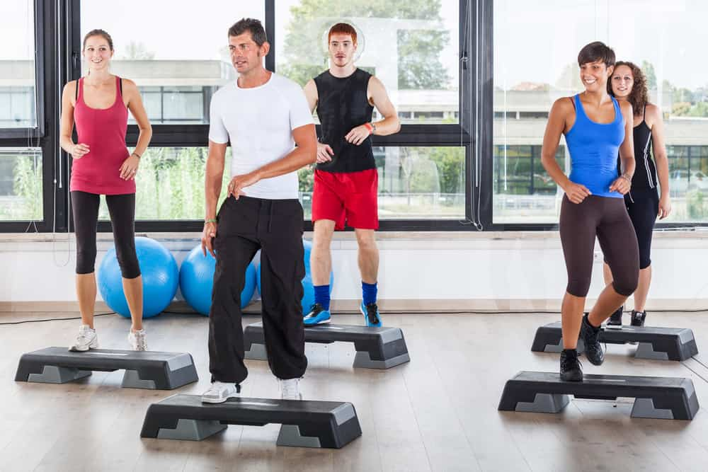 people in a group fitness step aerobics class