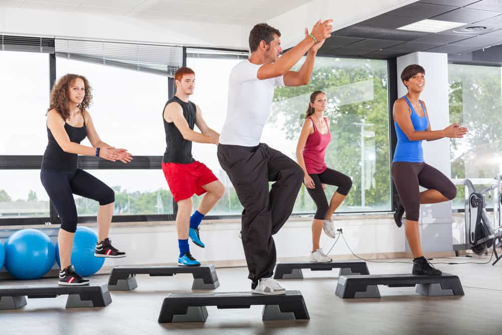 a group fitness class doing step aerobics, a decorative image in an article about step aerobics for beginners