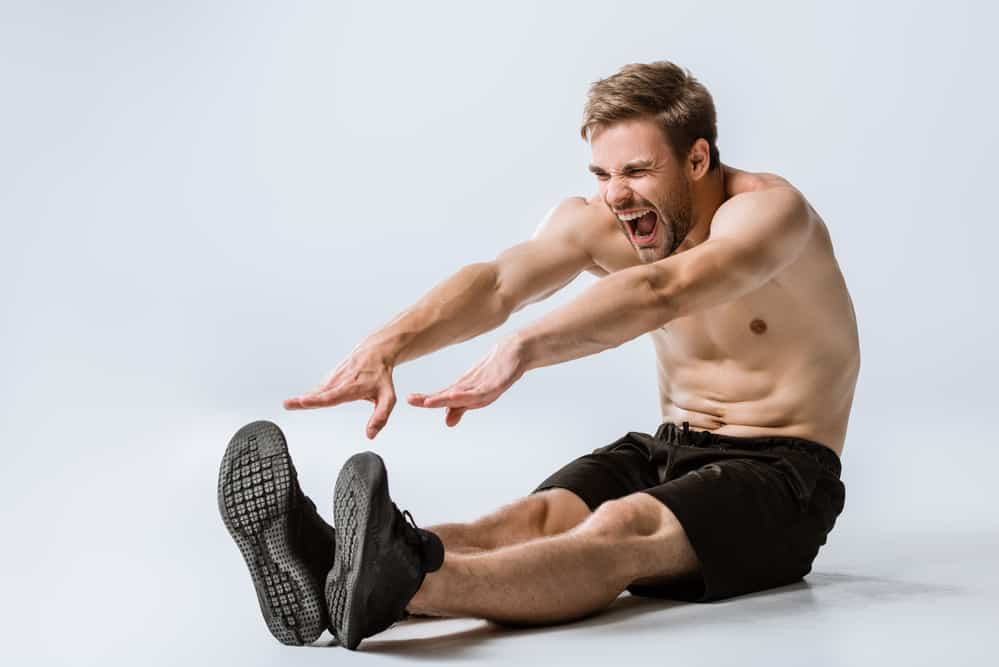 an athletic man struggling to stretch his hamstrings. decorative image in an article about how to avoid overstretching