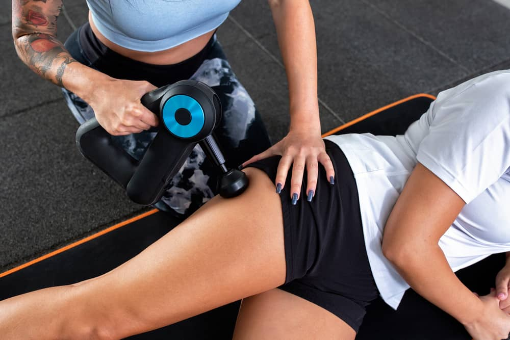 personal trainer using a massage gun on a client