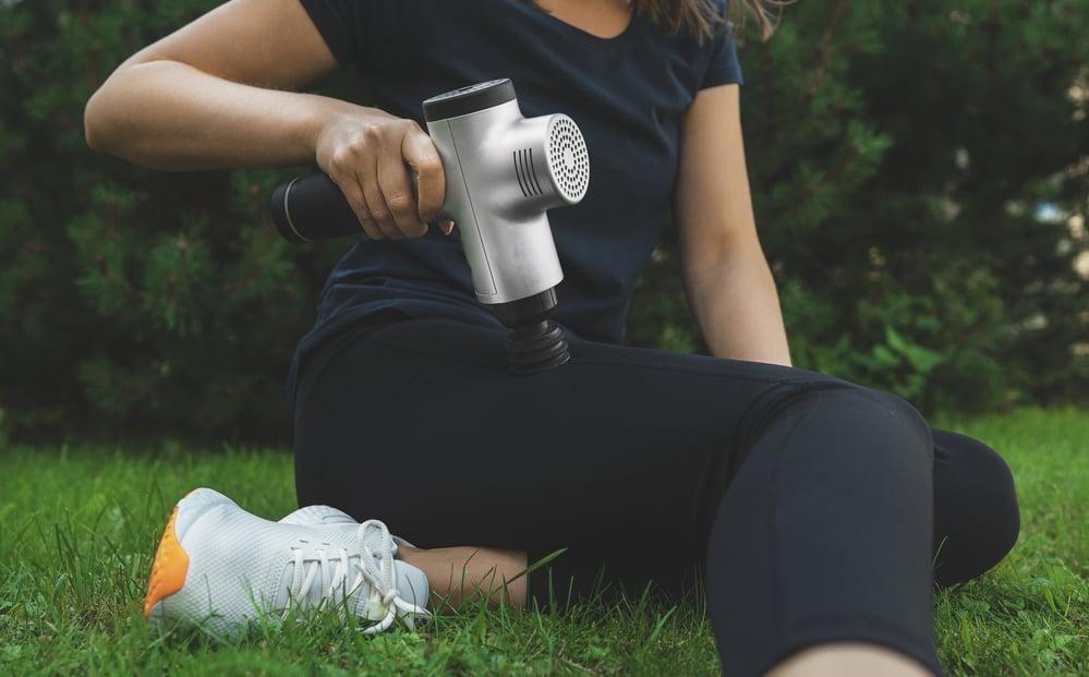 woman using a massage gun on her leg after a workout