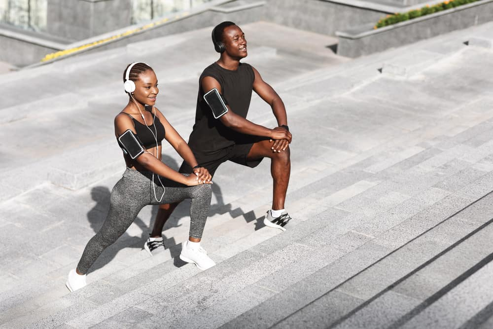 african american man and woman stretching outside during a workout