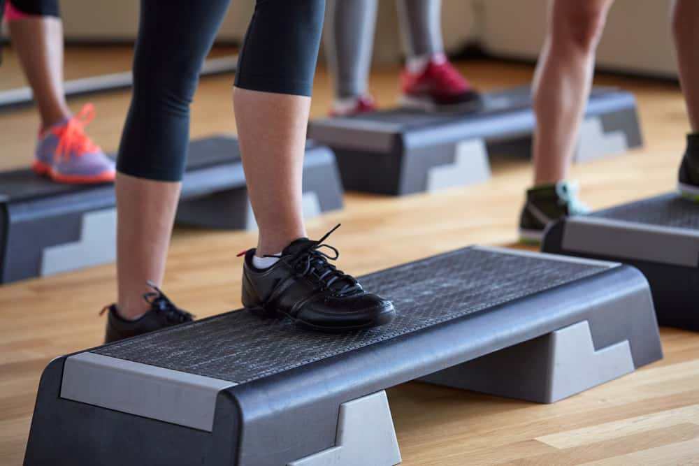woman in a step aerobics class with her foot on a step bench