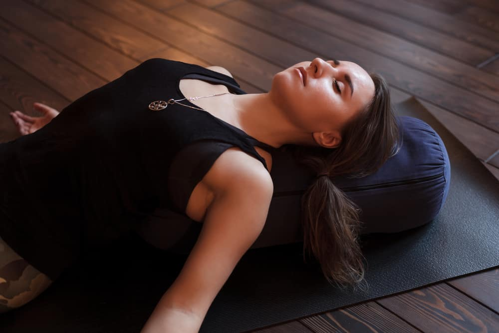 woman relaxing on a yoga bolster - decorative image in an article about gifts for yogis