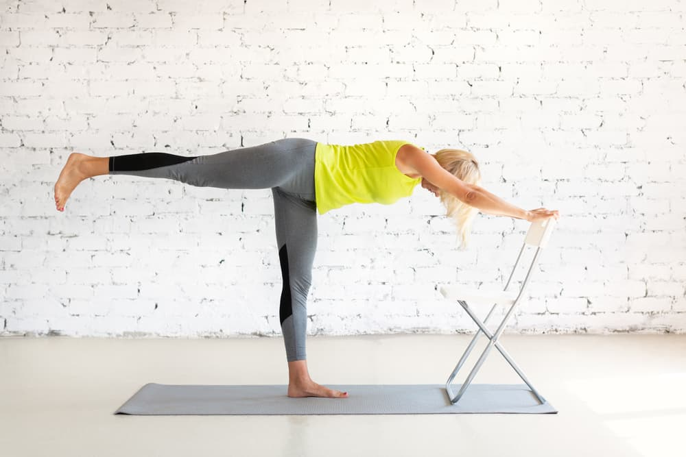 woman doing warrior 3 with the support of a chair