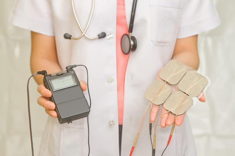 a doctor holding a tens unit as a decorative image in an article what do tens units do?