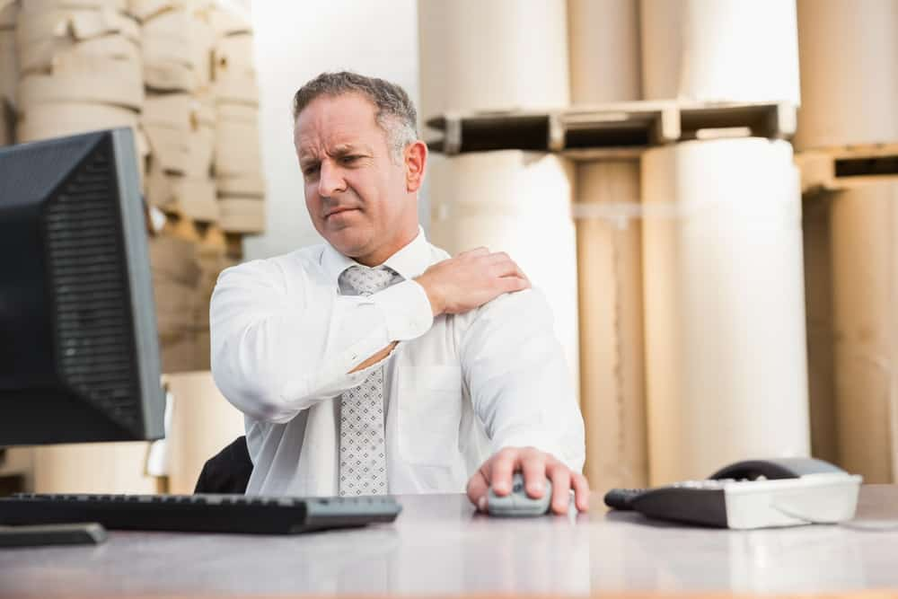 man working at a desk holding his shoulder in pain
